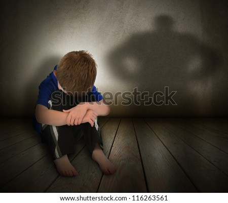 A young boy is sitting on the ground and scared with his face covered. There is a shadow silhouette on the wall to represent abuse, fear,  or a bully. - stock photo