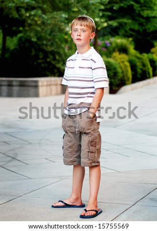 A young boy is standing outside on a sidewalk.  He is looking at the camera and has his hands in his pockets.  Vertically framed shot. - stock photo