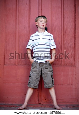 A young boy is standing up against a red wall.  He is looking away from the camera and has his hands in his pockets.  Vertically framed shot. - stock photo