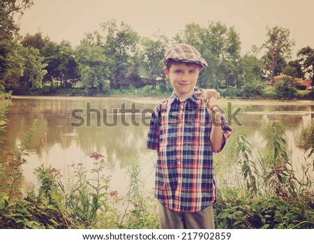 A young boy is wearing a cap hat and holding a wooden fishing pole by a pond of water for an activity or memory concept. - stock photo