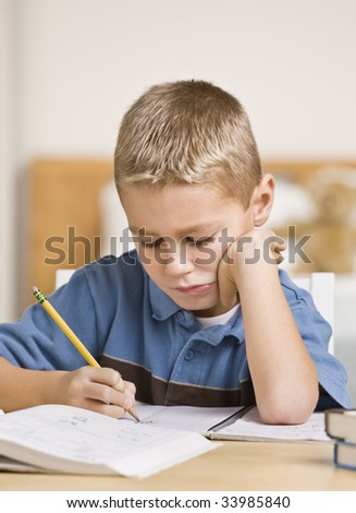 A young boy is working on his homework at the table.  He is looking down at what he is doing.  Vertically framed shot.