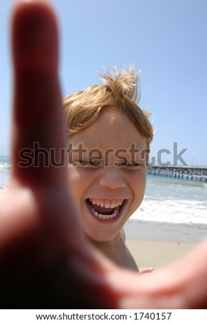 a young boy laughs and blocks the camera at the beach - stock photo