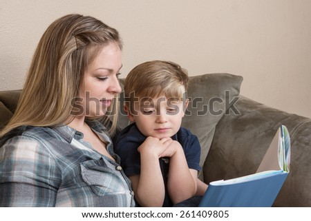 A young boy listens attentively as his mother reads to him.