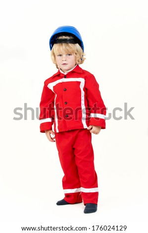 A young boy looking forward wearing blue hard hat and red jacket and pants. - stock photo