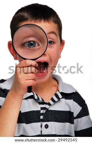 A young boy looking through a magnifying glass - stock photo