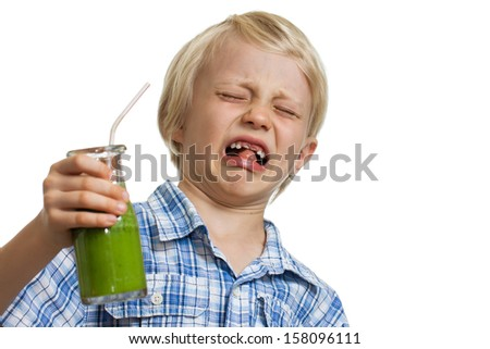 A young boy looking very disgusted holding a green smoothie. Isolated on white. - stock photo