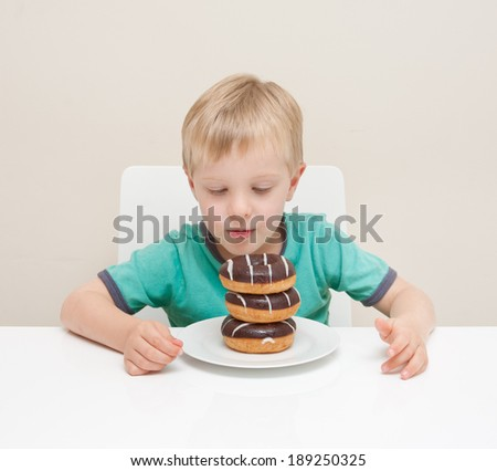 A young boy looks at his stack of chocolate donuts.  The child is isolated against a white background.