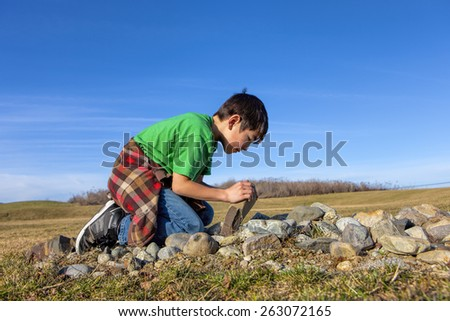 A young boy looks under a rock to see what is under there. - stock photo