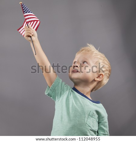 A young boy looks up at an American flag that he holds proudly above his head. - stock photo