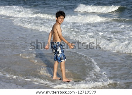 A young boy on a skim board. - stock photo
