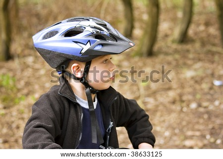 A young boy on a woodland trail wearing a cycle helmet