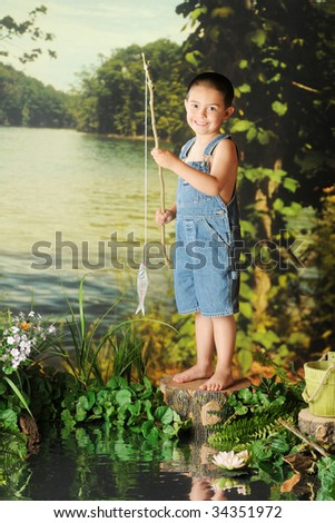 A young boy on overall shorts happily showing off a fish he caught from a pond. - stock photo