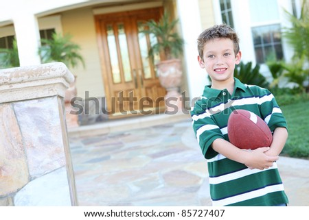 A young boy outside home holding football having fun - stock photo