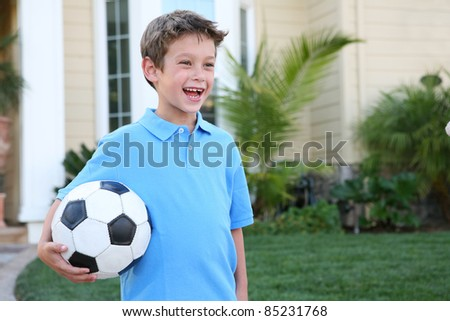 A young boy outside home holding soccer (football) ball - stock photo