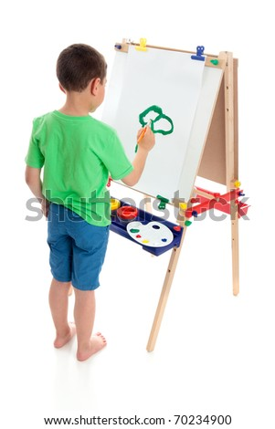 A young boy painting a picture on an art easel.  White background. - stock photo