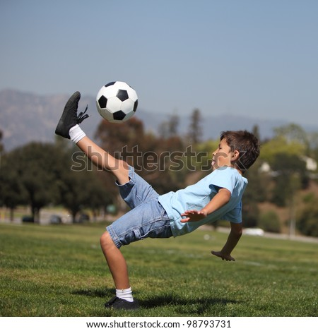 "A young boy performs a soccer ""bicycle kick"" in a park - stock photo"