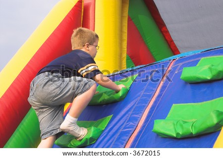 A young boy playing on a obstacle course. - stock photo
