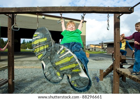 A young boy playing on a school playground. - stock photo