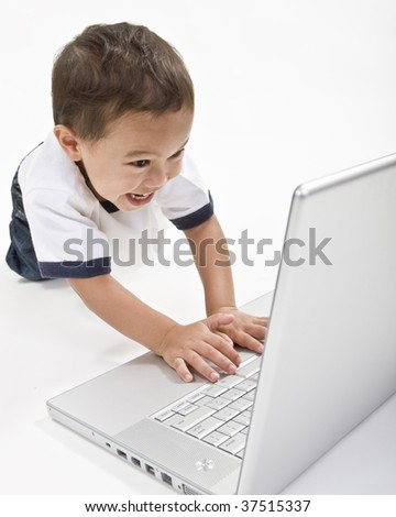 A young boy playing on his laptop