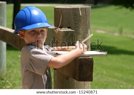 a young boy plays contractor while wearing a blue hard hat and taking notes on a clip board - stock photo