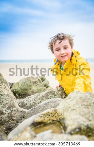 A young boy plays near a rock pool in the UK on a rainy summers day wearing a yellow mackintosh. - stock photo
