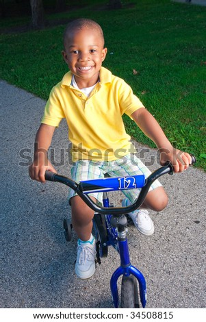 a young boy poses on his small bike - stock photo