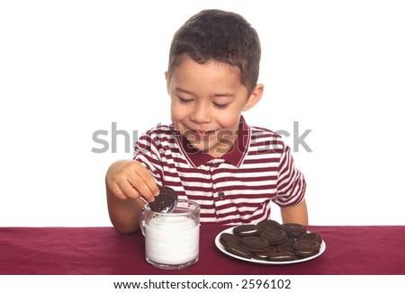 A young boy prepares to snack on cookies and milk
