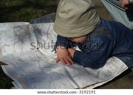 A young boy reading a map - stock photo