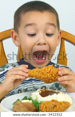 A young boy ready to devour his fried chicken - stock photo