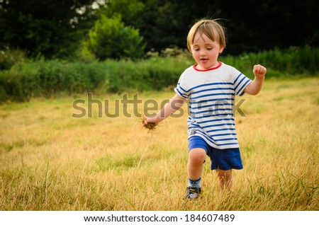 A young boy running in a field on a hot summers day - stock photo