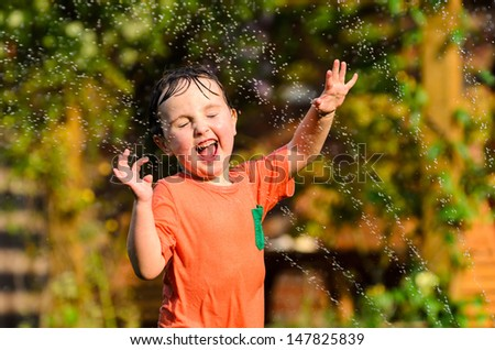 A young boy running through water from a sprinkler