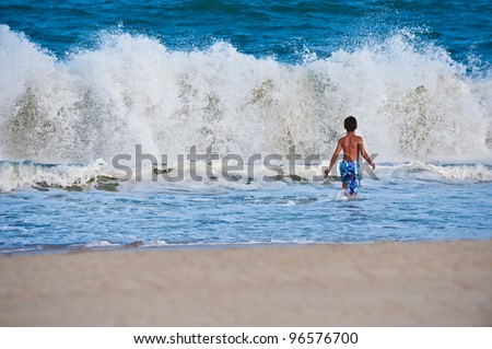 A young boy runs into the huge waves of the Atlantic Ocean while playing.  Cape Hatteras beach in North Carolina, USA in summer.