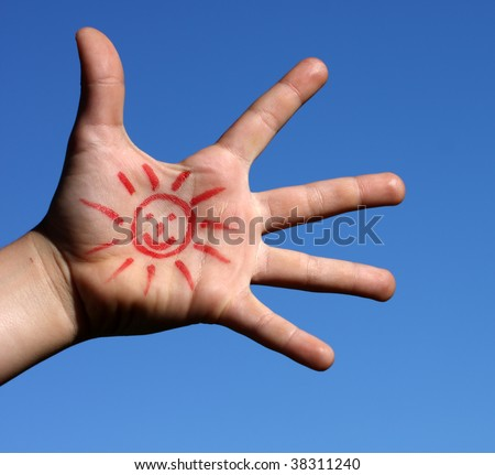 A young boy's hand with a drawing sun over a blue sky - stock photo