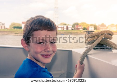 A young boy sat on the water bus crossing a river in the Netherlands