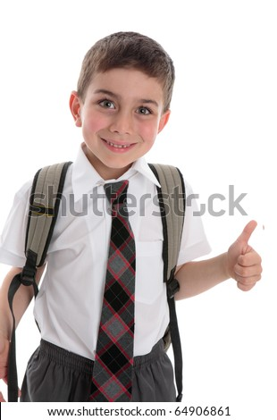 A young boy schoolboy wearing school uniform.  He is smiling and showing a thumbs up hand sign. - stock photo