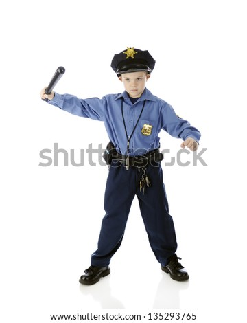 A young boy seriously wielding a billy club while wearing his policeman's uniform.  On a white background. - stock photo
