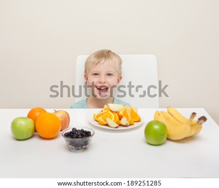 A young boy sits down to eat a plate of cut colourful fruit including apples, oranges, bananas, and blueberries.  The child eating healthy food is isolated against a white background.