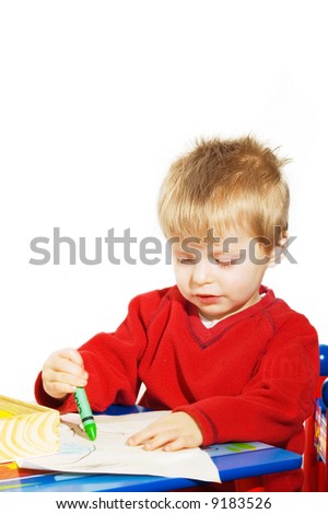 A young boy sitting at a desk writing with his crayons. - stock photo