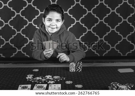 A young boy sitting at a poker table gambling playing cards in black and white - stock photo