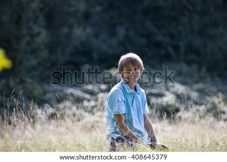 A young boy sitting in long grass, smiling - stock photo