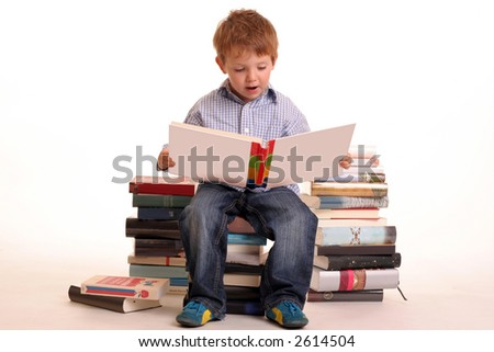 A young boy sitting on a pile of books practising - stock photo