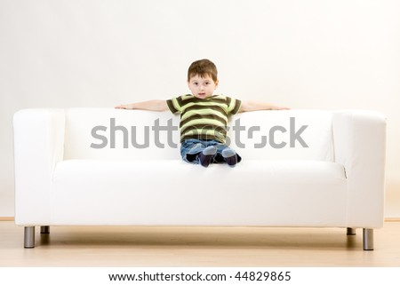 A young boy sitting on a white couch.