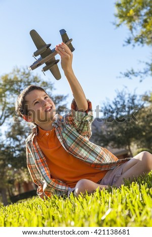 A young boy sitting on grass outside playing with a toy model airplane
