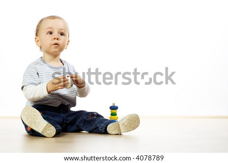 A young boy sitting on the floor, playing with his toys.