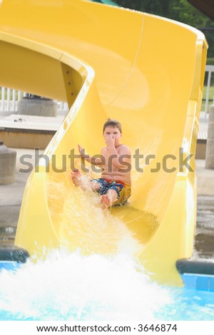 A young boy sliding down a water slide. - stock photo