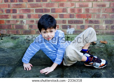 A young boy slips over and falls on his bottom. - stock photo