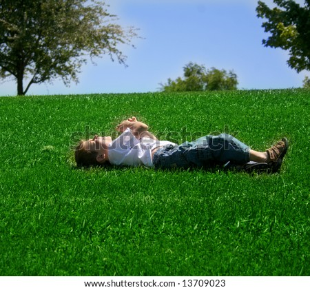a young boy squints in the sunshine as he rolls down a grassy hill - stock photo