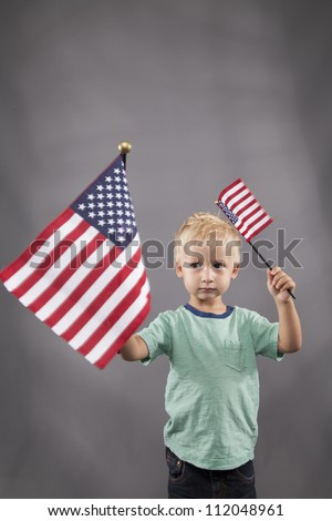 A young boy stands and waves two flags in his hands. - stock photo