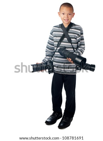 A young boy stands with cameras and a telephoto lens, in his father's shoes. - stock photo