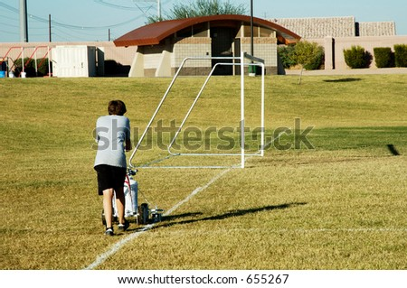 A young boy stripes the soccer field before a game. - stock photo